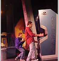 Photo of Alex playing the game in a musical based on The Last Starfighter, a video game themed movie by Universal 1984