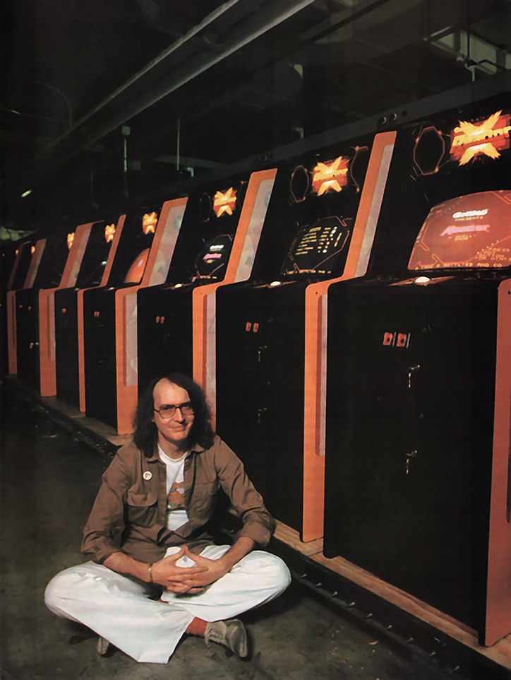 Tim Skelly poses with Reactor cabinets, an arcade video game by Gottlieb 1982