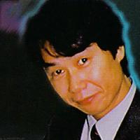 Shigeru Miyamoto posing with the Nintendo 64 video game console