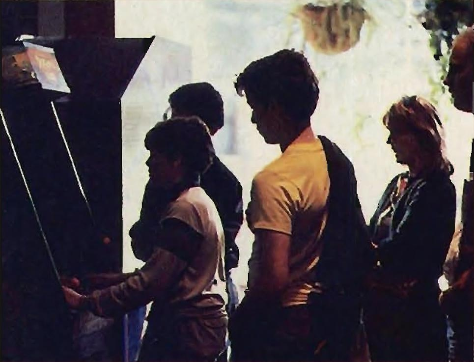 Crowd watches boy play Dragon's Lair, a laserdisc arcade game by Don Bluth