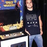 Van Halen bass player next to 'Space Invaders' machine, an arcade video game by Namco and Midway 1978