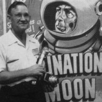 In front of a Destination Moon poster stands author E.E. Smith, SF author whose works were an inspiration for the video game Spacewar!