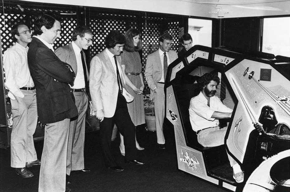 Onlookers watch George Lucas play Atari's Star Wars arcade game, 1983.